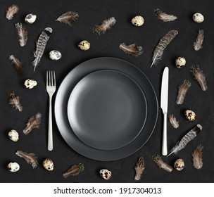 Table setting with a black plate, quail eggs and feathers on a black background. Easter concept. View from above.