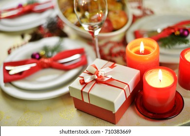 table setting  with candles. fork, knife and red napkin on dish