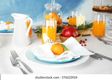 Table setting with candles and fruits