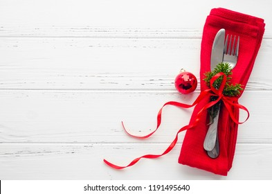 Table setting for celebration Christmas and New Year Holidays on white wooden table.. Festive place setting for christmas dinner with red napkin and natural decorations. Top view. Copy space.