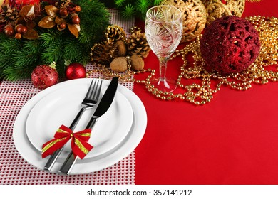 Table setting with Christmas decoration on red tablecloth background