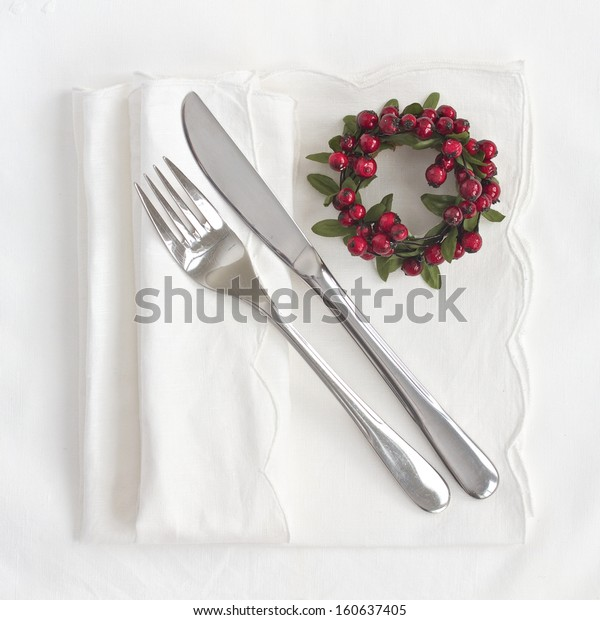 Table setting for Christmas with knife and fork and red wreath