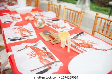 Table setting for a classic Swedish crayfish party with mallets, cheese slicers and crayfish bibs, outdoors under a tent