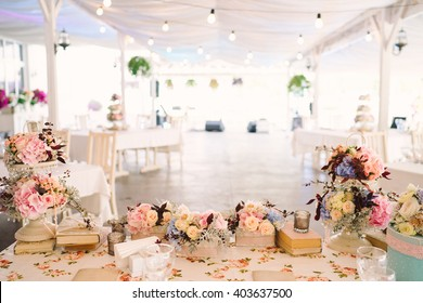 Table setting at country wedding reception, floral decoration, wrapped books and candles. Overhead view.