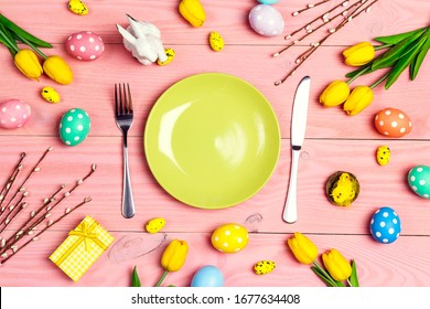 Table setting with cutlery and easter decorations on pink wooden table. Top view, space for text.