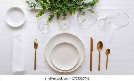 Table setting for elegant festive dinner with white porcelain plates, glasses, decorative textile gold cutlery and center place.