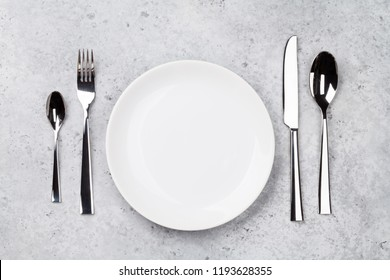 Table setting. Empty plate, knife, fork and spoons. Top view and flat lay with copy space