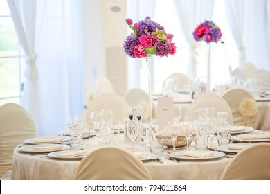 Table setting for an event party. White table with colored flowers on top