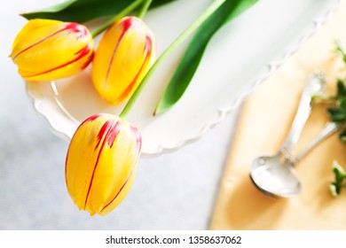 Table setting featuring Easter spring flowers - yellow fresh cut tulips.