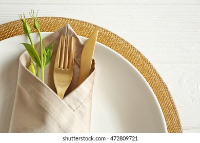 Table setting with fork and knife in napkin, closeup