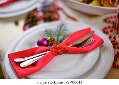 table setting . fork, knife and red napkin on dish