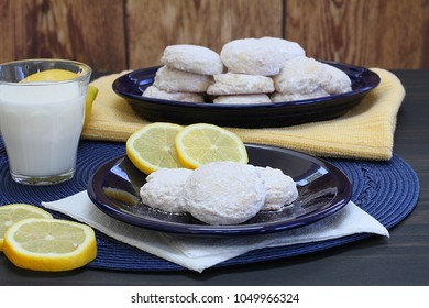 Table setting of fresh lemon cookies, lemon slices, and a glass of milk.  Three cookies in front with a full platter in the background.