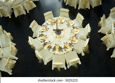 Table setting with golden plates and heart shapes on napkins plus scattered fresh rose petals for a wedding or romantic dinner event