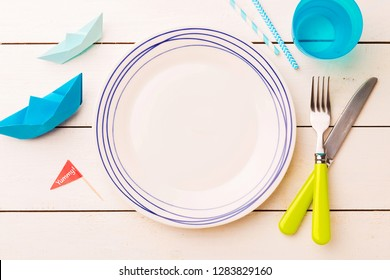 Table setting for kids. Empty plate on white planked wooden table with colorful decorations around - captured from above (top view, flat lay).