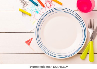 Table setting for kids. Empty plate on white planked wooden table with colorful decorations around - captured from above (top view, flat lay). Layout with free text (copy) space.