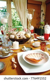 Table setting in marine style, with candles, sea shells and cand