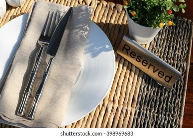 "Table setting in morning sunlight. Top view and medium closeup of fork, knife and napkin put on white porcelain plate. With pepper and salt holder, ""reserved"" all set on plant fiber plate mat."