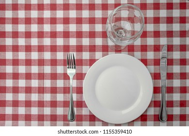 Table setting on a red gingham pattern table cloth. Knife, fork, dish and wineglass on a gingham table cloth.