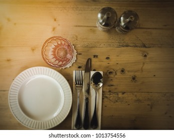 Table setting on vintage theme with plate, fork, glasses with salt and pepper give homey and delicious dining feeling.