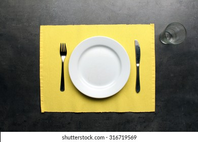 Table setting for one person on dinning table, top view