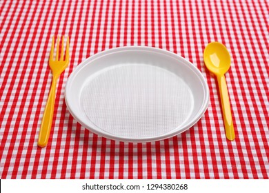 Table setting with plastic dishware on plaid fabric