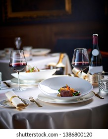 table setting with plate of beef with glasses of red wine