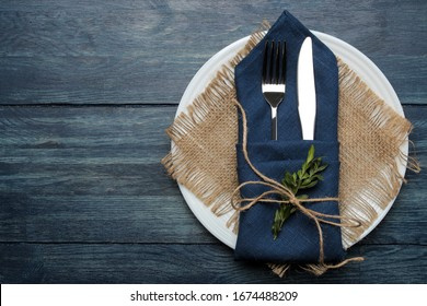 Table setting. plate and cutlery in a blue napkin, fork and knife on a blue wooden table. top view