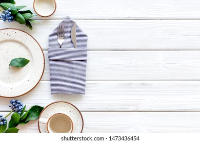 Table setting with plates, flatware and flower on white wooden background top view copy space