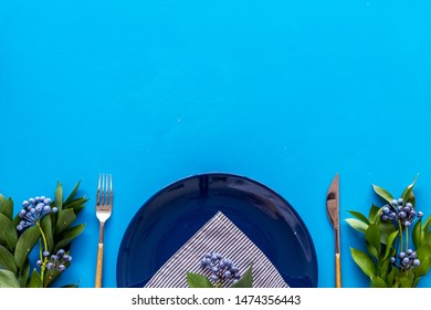 Table setting with plates, flatware and flower on blue background top view copy space