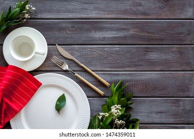 Table setting with plates, flatware and flower on wooden background top view copy space