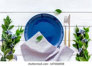 Table setting with plates, flatware and flower on white wooden background top view