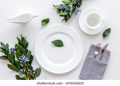 Table setting with plates, flatware and flower on white background top view