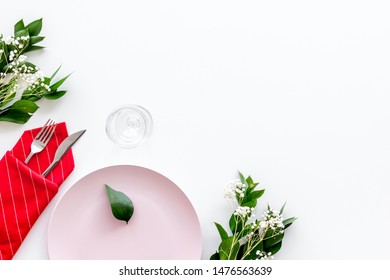 Table setting with plates, flatware and flower on white background top view copy space