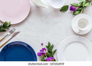 Table setting with plates, flatware and flower on marble background top view copy space