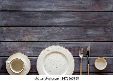 Table setting with plates and flatware on wooden background top view copy space