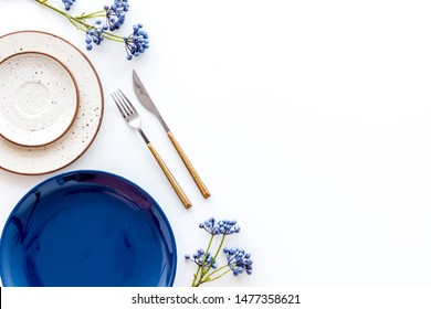 Table setting with plates and flatware on white background top view mockup