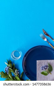 Table setting with plates and flatware on blue background top view mockup