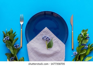 Table setting with plates and flatware on blue background top view