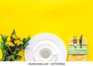 Table setting with plates and flatware on yellow background top view mockup