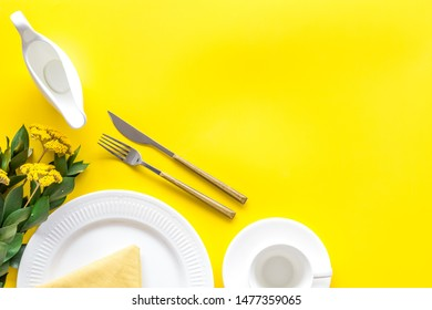 Table setting with plates and flatware on yellow background top view mock up