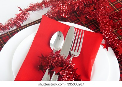 Table setting in red christmas colors with linen tablecloth and silverware