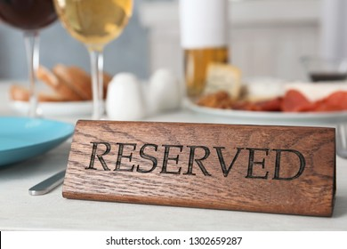 Table setting with RESERVED sign in restaurant