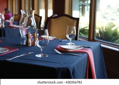 Table setting in  a restaurant with a blue tablecloth, red napkins and white plates