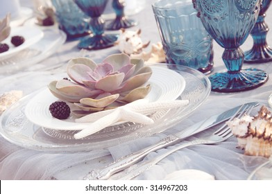Table setting for seaside dinner with succulent plants
