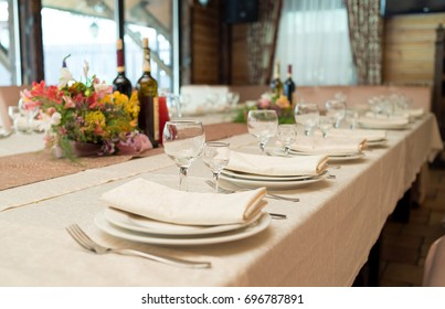 Table setting, selective focus. Table served for wedding banquet, close up view. Beige serviette on white empty plate on dinner table