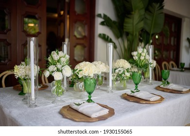 Table setting with serviette and greens, wooden plates and green glasses, with vases with white flowers and candles
