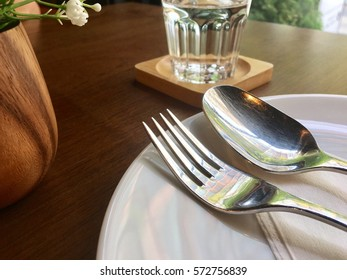 table setting, spoon and fork on white plate with a glass of water and flower