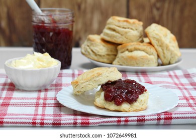 Table setting of strawberry jam and fresh homemade biscuits.