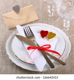 Table setting for Valentine's Day with plates, knife, fork,wine glasses, napkin,red ribbon and hearts