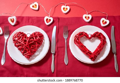 Table setting for Valentine's day, wedding cutlery, romantic dinner, declaration of love, love confession, date. Vintage tableware on the red background with heart-shaped lights, two red hearts